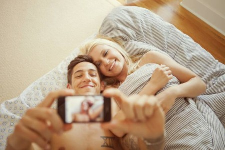 Couple taking pictures of themselves in bed