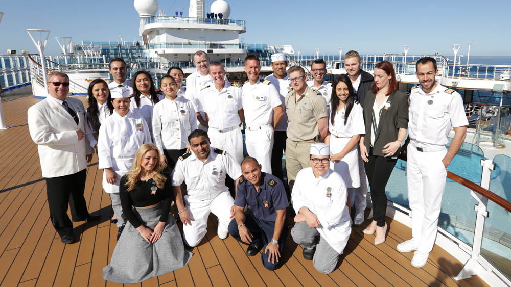 "FROM WILD PICTURES  THE CRUISE  Thursday 3rd March 2016 on ITV  Pictured:The crew of the Regal Princess on deck With unique access to one of the world's largest luxury cruise ships, this new series follows life on board for the crew of 1400 who live and work on board the Regal Princess for up to 9 months at a time; from battling leaks to seeking promotions and from tense navigation challenges to trying to keep their relationships afloat. Tonight, as the 11 day voyage around the Baltic from Copenhagen to St Petersburg begins, the guests have more than relaxing on their mind – they're vying for the coveted award of the most travelled passenger.  Some cruise superfans have spent up to 7 or 8 years of their lives aboard. Martha & Rusty Underwood are in the running but say ""These people have so many cruises, the only way we will ever catch up is if they die and we don't!"" The crew's entertainment team is joined by new dancer Dulcie, from Portsmouth, but will she make the grade as a professional dancer?  The inimitable Timothy is charming passengers on the front desk but has his eye firmly on a job with 'ship bestie' Emma doing shore excursions.  And ex navy engineer Scott, from Darlington, joins the engineering team and soon has to find the source of a leak – no mean feat when you're dealing with hundreds of miles of pipes.  © Wild Productions  For further information please contact Peter Gray 0207 157 3046 peter.gray@itv.com   This photograph is © ITV and can only be reproduced for editorial purposes directly in connection with the  programme THE CRUISE or ITV. Once made available by the ITV Picture Desk, this photograph can be reproduced once only up until the Transmission date and no reproduction fee will be charged. Any subsequent usage may incur a fee. This photograph must not be syndicated to any other publication or website, or permanently archived, without the express written permission of ITV Picture Desk. Full Terms and condition"