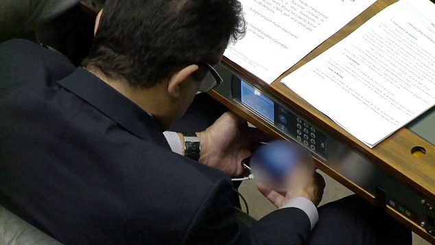 """Pic shows: The MP watching porn in the Brazilian Parliament. A Brazilian MP has been caught watching a pornographic video on his mobile phone during a lower house session of the local Parliament. The legislator Joao Rodrigues, of the ruling Social Democratic Party, appears to be watching a video on his phone, hidden under his desk, and at times even appears to share it with other legislators who approach his seat. Local media also released an image of what was recorded from his mobile screen, allegedly of women """"in obscene positions, very obscene."""" While he was watching the video, Rodrigues had on his desk an invitation to attend a mass at the headquarters of Bishops of Brazil. At the time of the incident, the Chamber of Deputies was in full session debating and voting on electoral reform. Rodrigues, on Facebook, said he received the video through a group conversation on Whatsapp and was on the verge of deleting it. """"I participate in nearly a hundred groups on WhatsApp and during the day I search and separate the wheat from the chaff. What interests me I keep or forward and what doesn't interest me, I delete. It was just what I was doing, erasing the rubbish,"""" he explained. The legislator said that not only did he erase the video, but also blocked the sender as the video annoyed him. (ends)"""