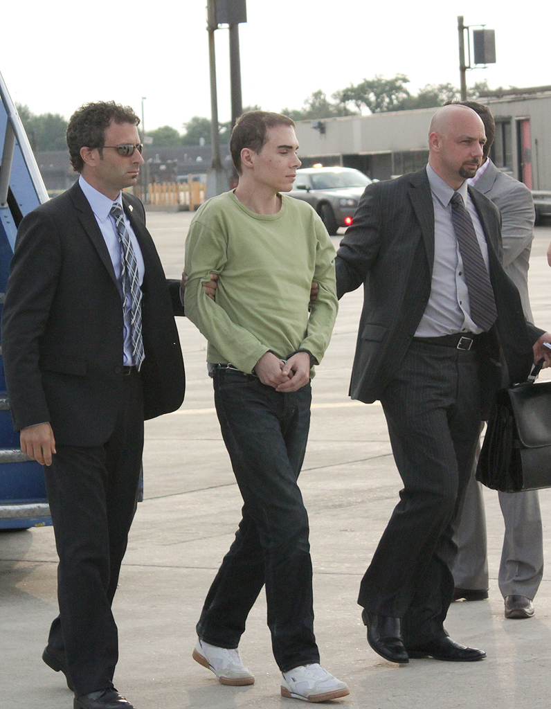 "This photograph obtained courtesy of the Service de Police de la Ville de Montreal (SPVM) shows Luka Rocco Magnotta (C) escorted by police upon arrival from Germany on June 18, 2012 at Mirabel Airport outside Montreal on June 18, 2012 in Mirabel, Quebec, Canada. Magnotta, dubbed ""the Canadian Psycho"", is accused of slaying and dismembering a Chinese student in Montreal last month, before fleeing to Europe. AFP PHOTO / Service de Police de la Ville de Montreal == RESTRICTED TO EDITORIAL USE / MANDATORY CREDIT: ""AFP PHOTO / Service de Police de la Ville de Montreal"" / NO SALES / NO MARKETING / NO ADVERTISING CAMPAIGNS / DISTRIBUTED AS A SERVICE TO CLIENTS =="