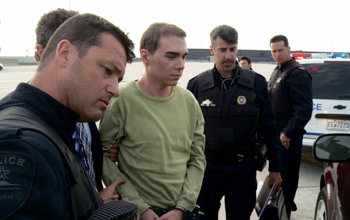 JUNE 18, 2012 FILE PHOTO; AP PROVIDES ACCESS TO THIS PUBLICLY DISTRIBUTED HANDOUT PHOTO PROVIDED BY MONTREAL POLICE. FILE - In this Monday, June 18, 2012 file photo provided by Montreal Police, Luka Rocco Magnotta is taken by police from a Canadian military plane to a waiting van in Mirabel, Quebec. Magnotta, a Canadian porn actor accused of dismembering his Chinese lover and mailing the body parts to political parties and schools collapsed in court during his preliminary hearing Tuesday, March 13, 2013. (AP Photo/Montreal Police, File)